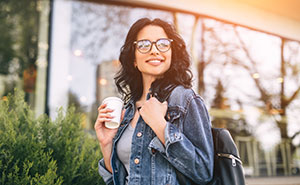 brunette woman with glasses and jean jacket smiling