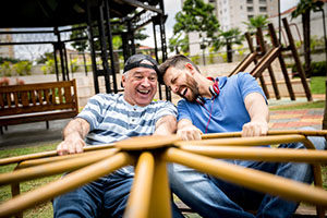 Two men spinning on a playground roundabout