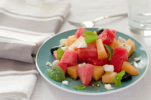 mixed melon chunks with feta cheese served on a plate