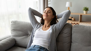woman relaxing on the couch with her eyes closed and hands behind her head